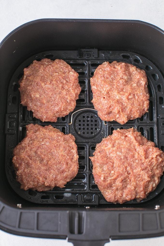 uncooked burgers in air fryer basket