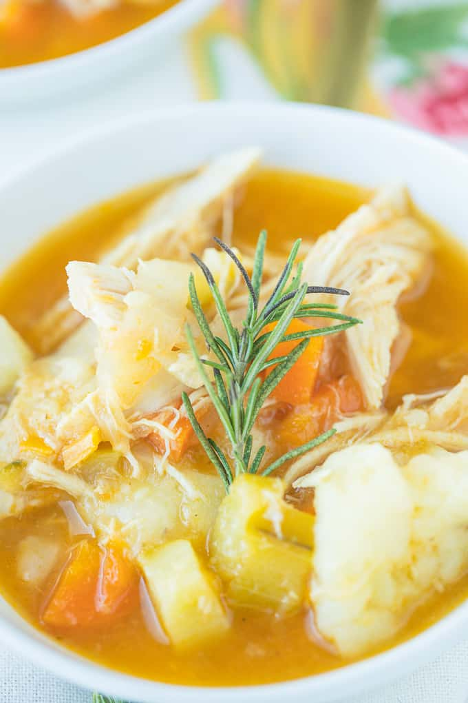bowl of turkey soup with vegetables and mashed potatoes