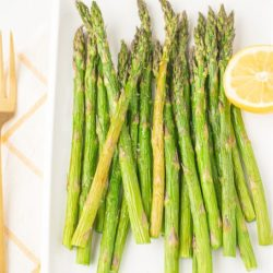 air fried asparagus on a plate with two gold forks