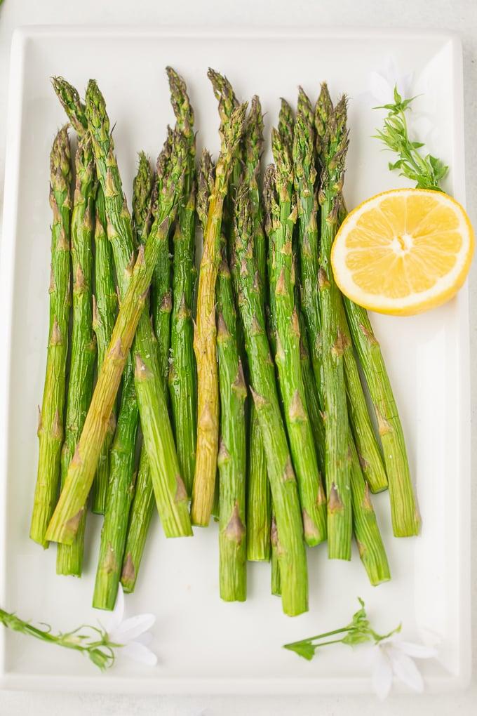 air fryer asparagus on a serving platter with fresh lemon