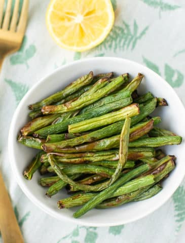 air fryer green beans in a white bowl with a lemon and gold forks