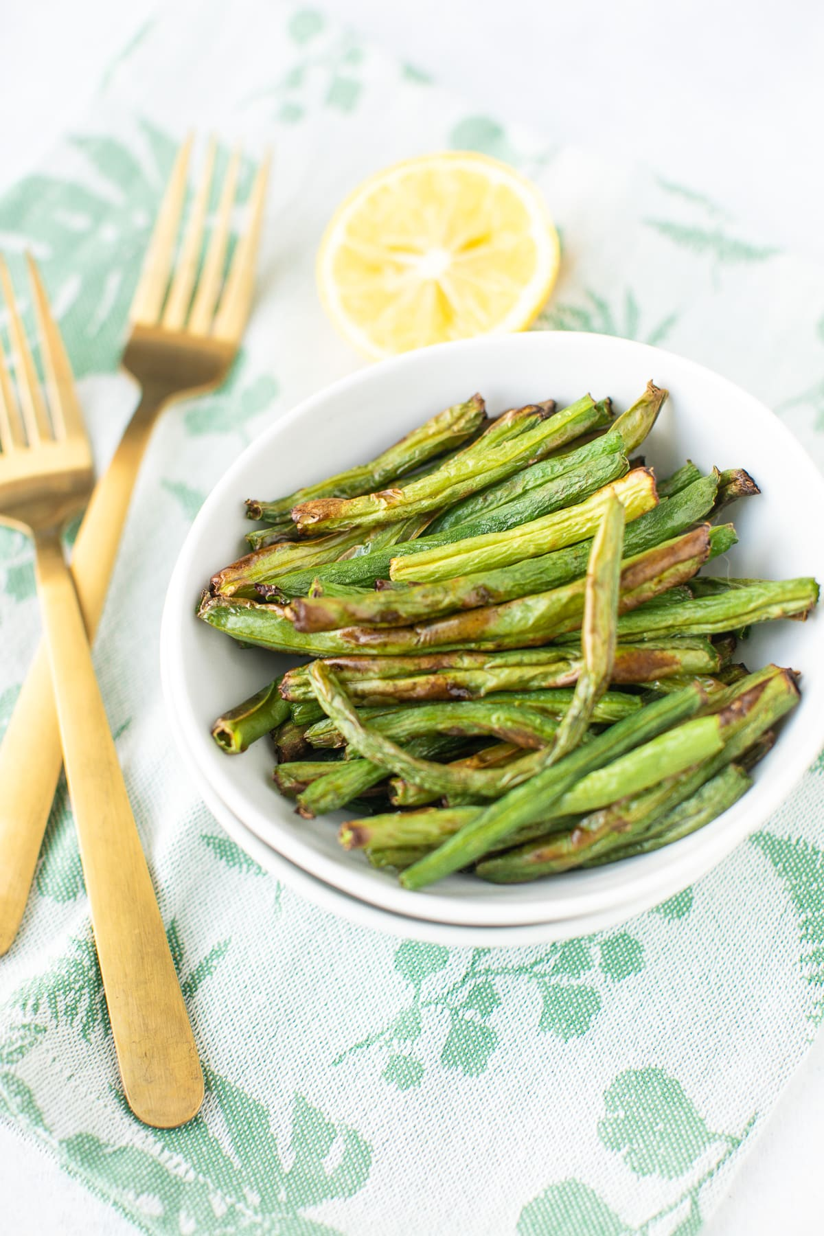 green beans in a bowl with two gold forks