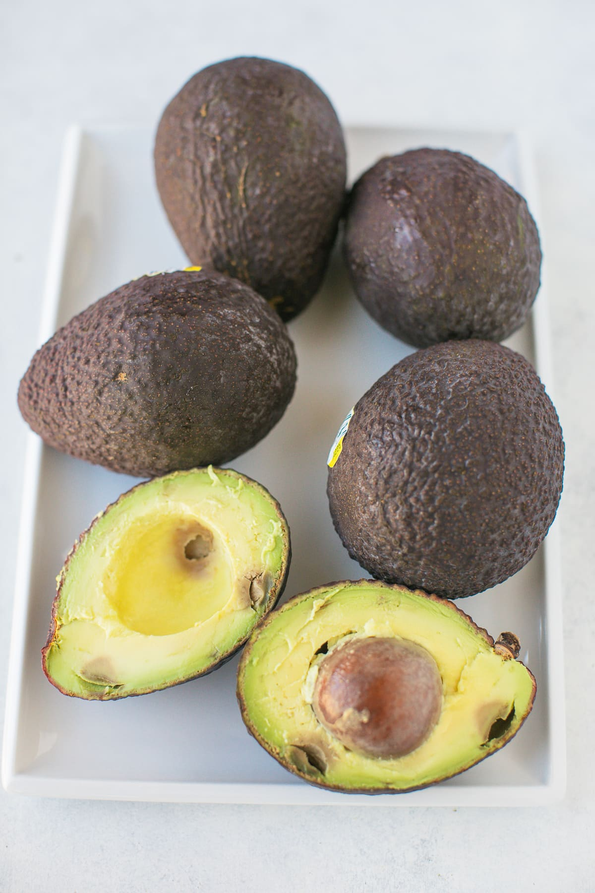 avocados on a white platter with one cut in half