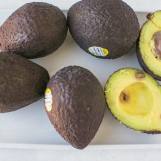 ripe avocados on a white platter