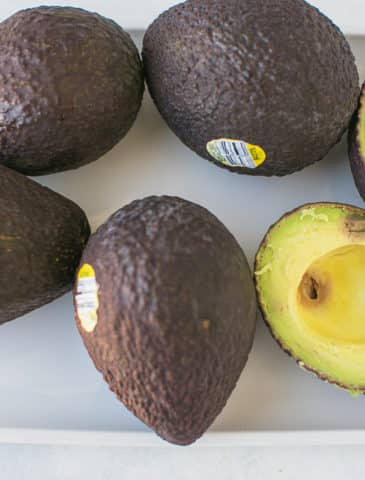 ripe avocados on a white platter