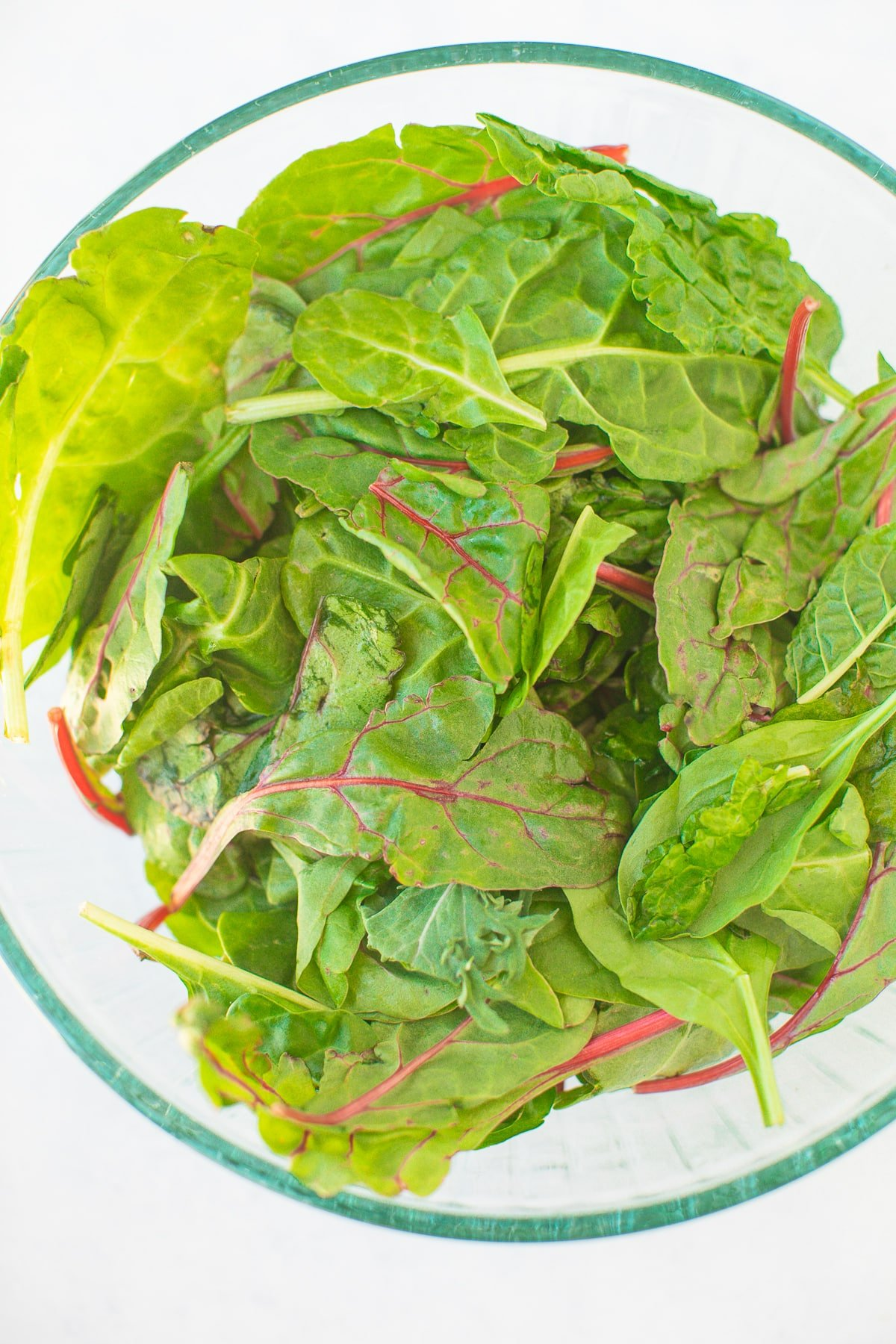 baby spinach, kale, and swiss chard in a glass bowl