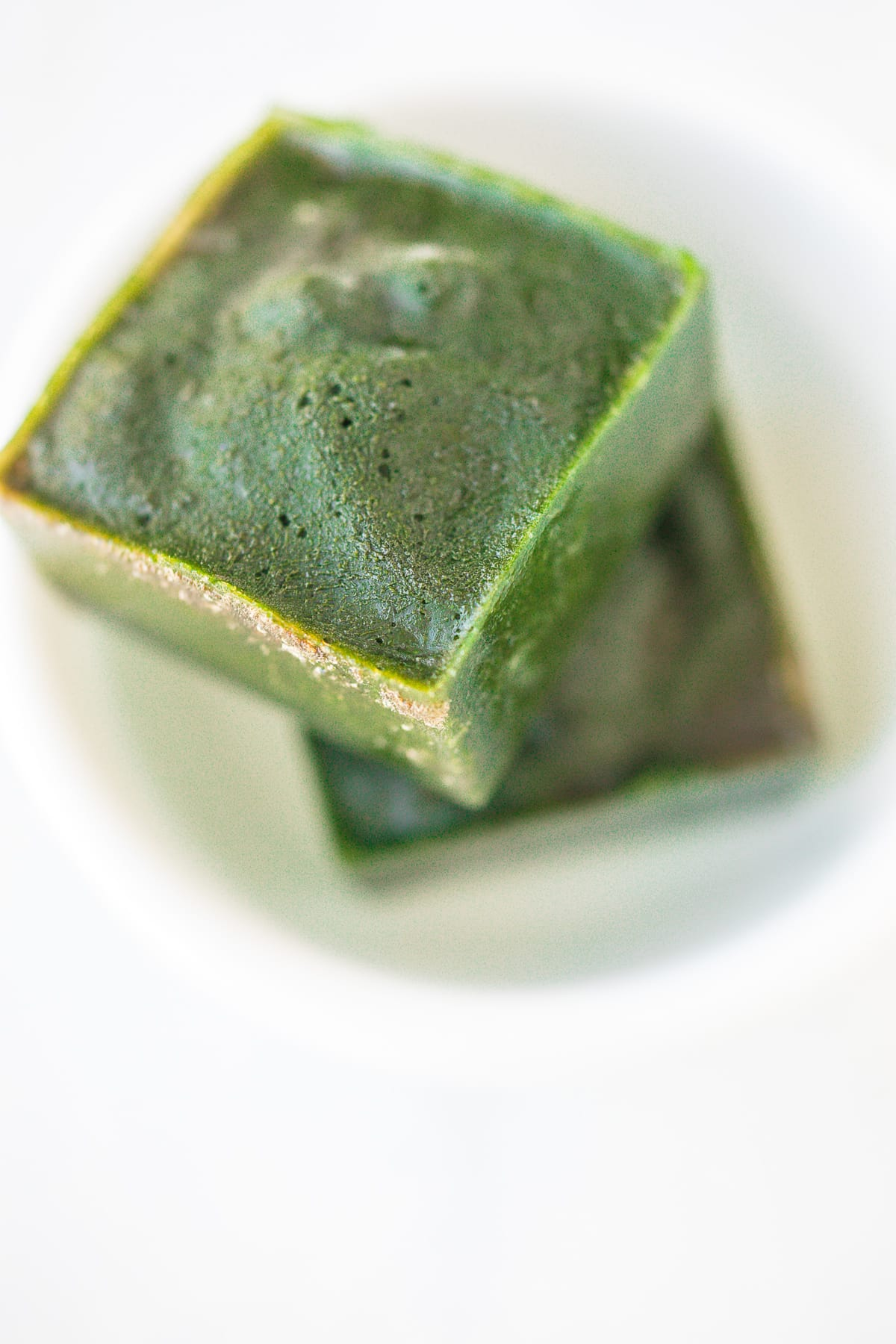 two spinach ice cubes in a white bowl