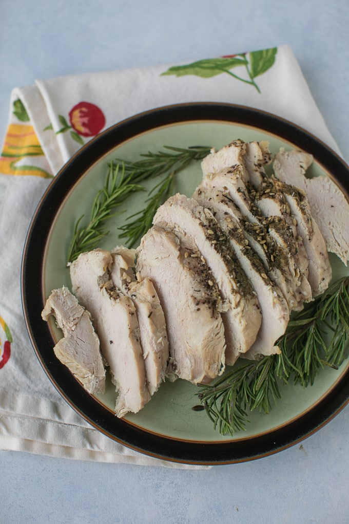 sliced turkey on a plate with fresh rosemary