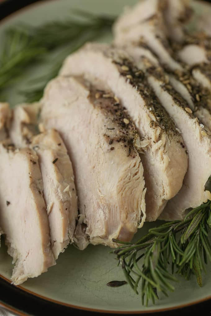 sliced turkey breast on a plate with fresh rosemary