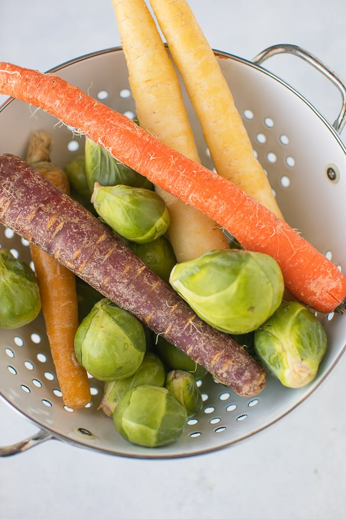 carrots and brussels sprouts in a white colander