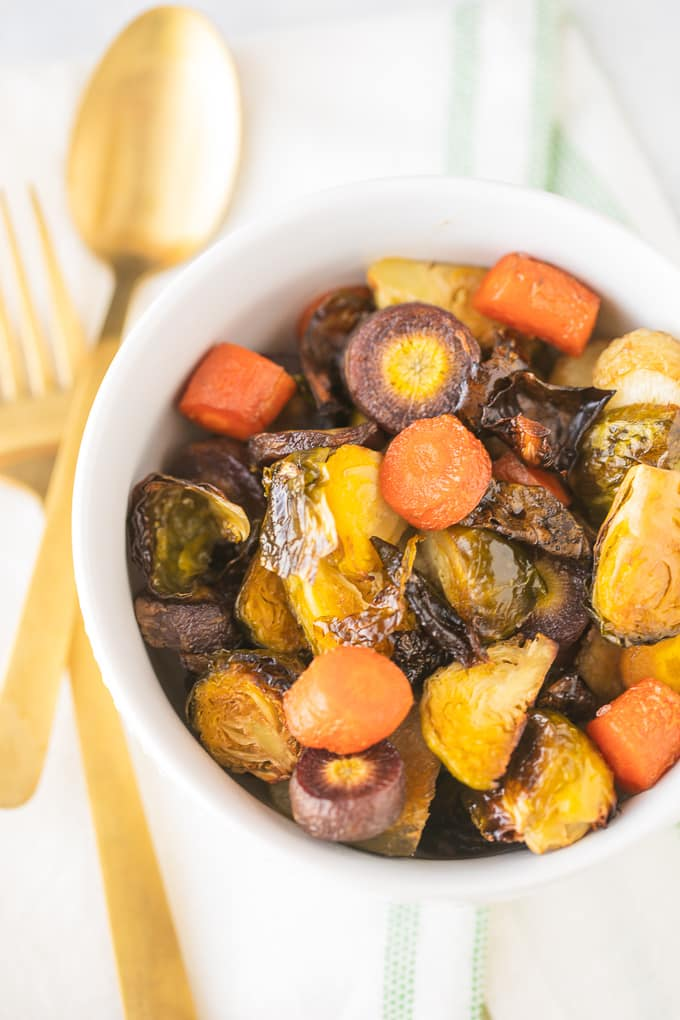 roasted vegetables in a white bowl with a gold fork and spoon