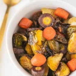 bowl of roasted brussels sprouts and carrots ready to eat