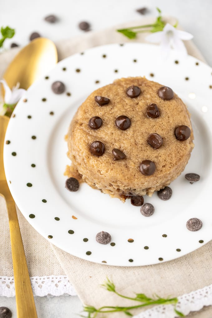 chocolate chip mug cake served on a plate with a gold spoon