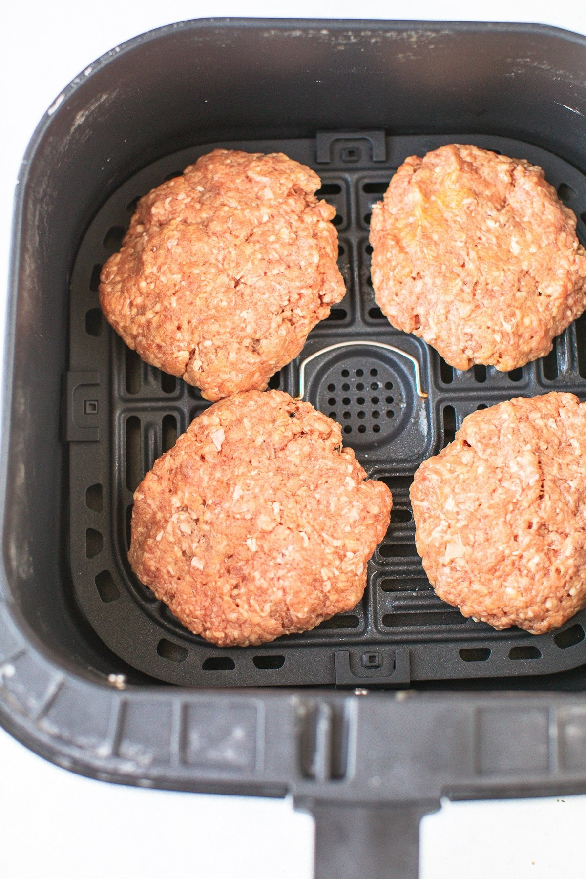 hamburger patties ready to be cooked in air fryer basket