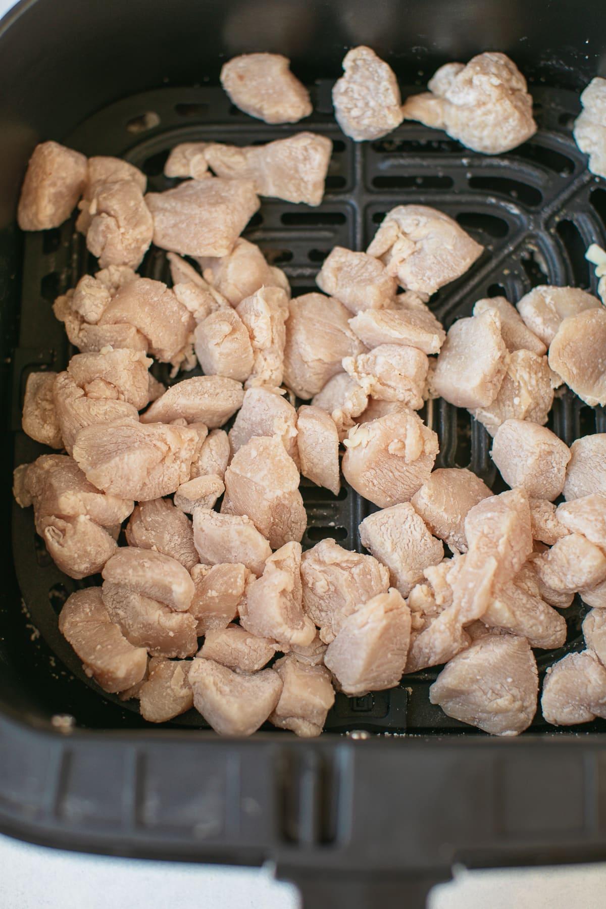 chicken in the basket of an air fryer