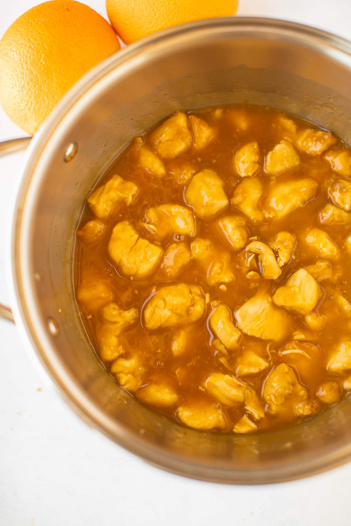 saucepan with chicken and orange sauce