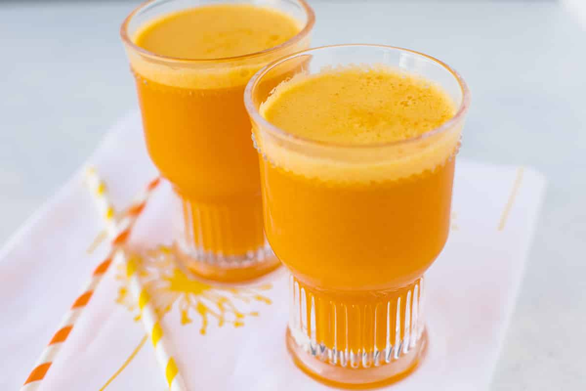 two glasses of juice with striped straws