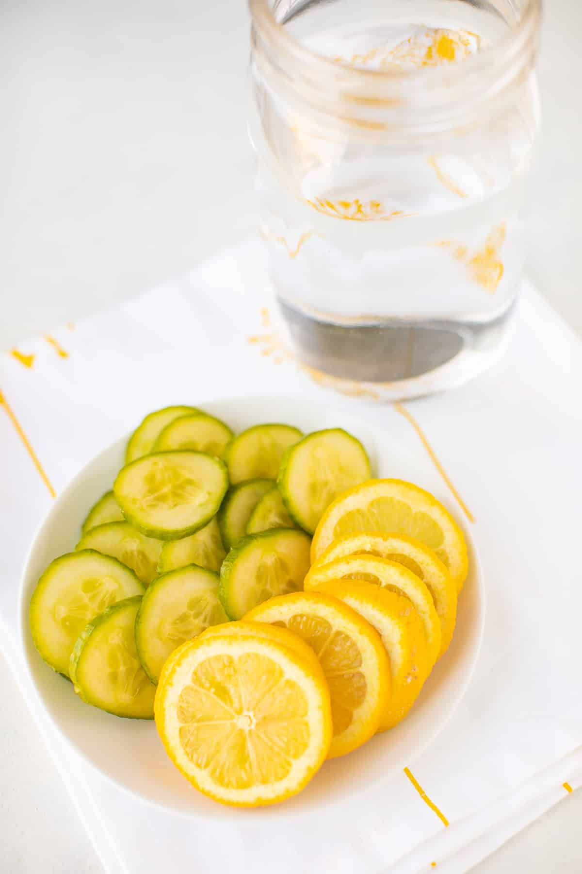 jar of water with sliced lemons and cucumbers