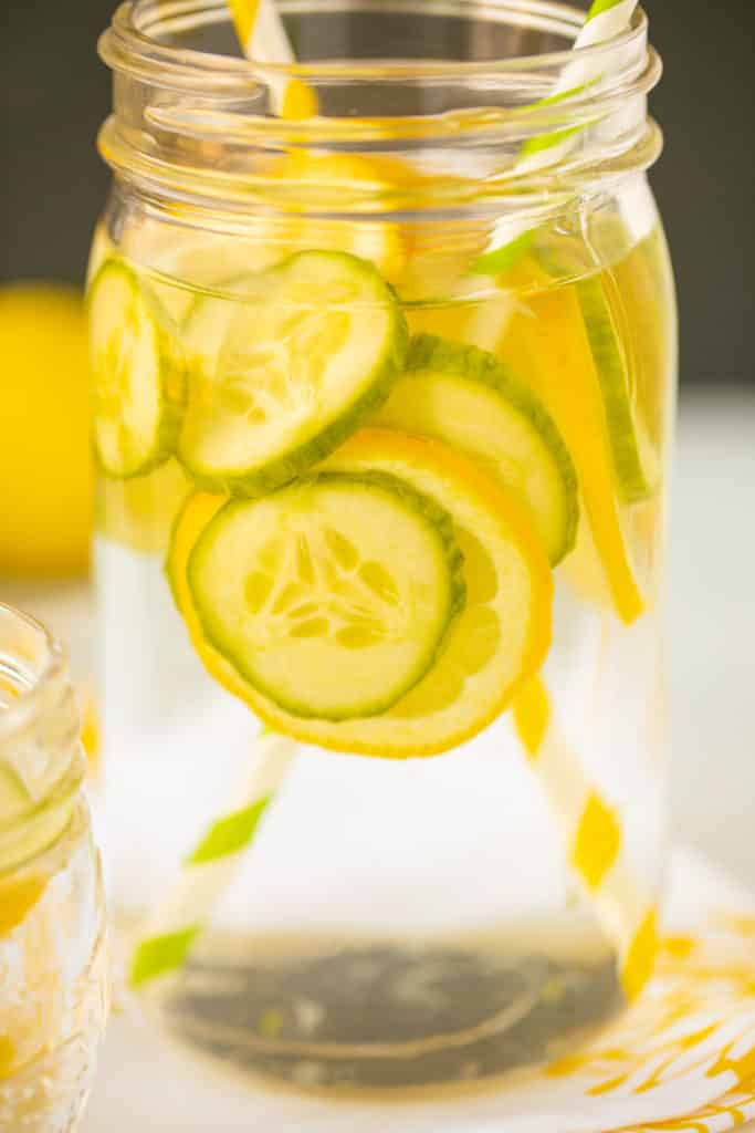 mason jar with lemon and cucumber slices floating in water
