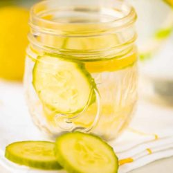small jar of water with sliced cucumber and lemons