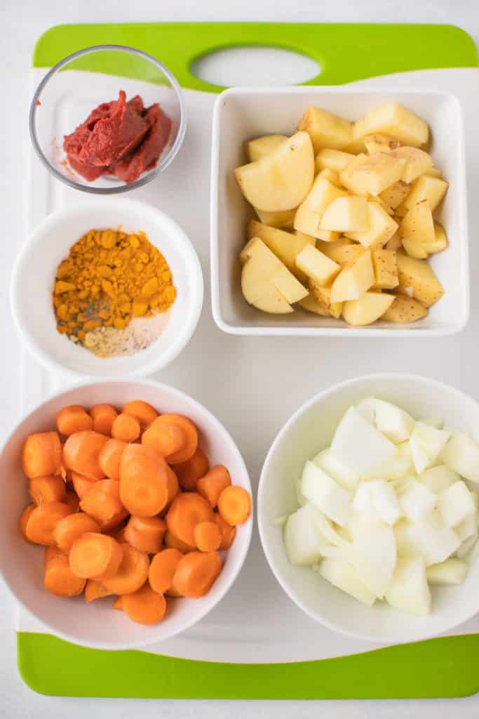 vegetable ingredients for the curry in white bowls