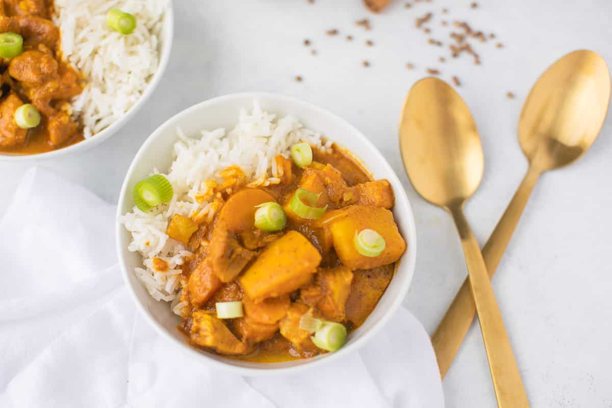 bowl of curry with two gold spoons