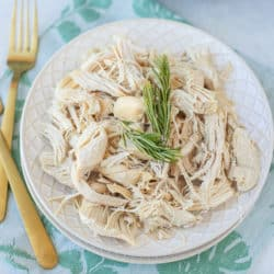 bowl of shredded chicken with two gold forks