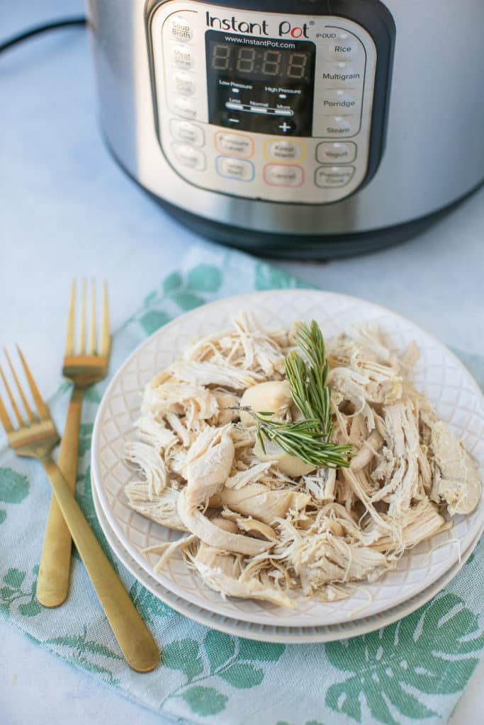 shredded chicken on a plate with the Instant Pot in the background