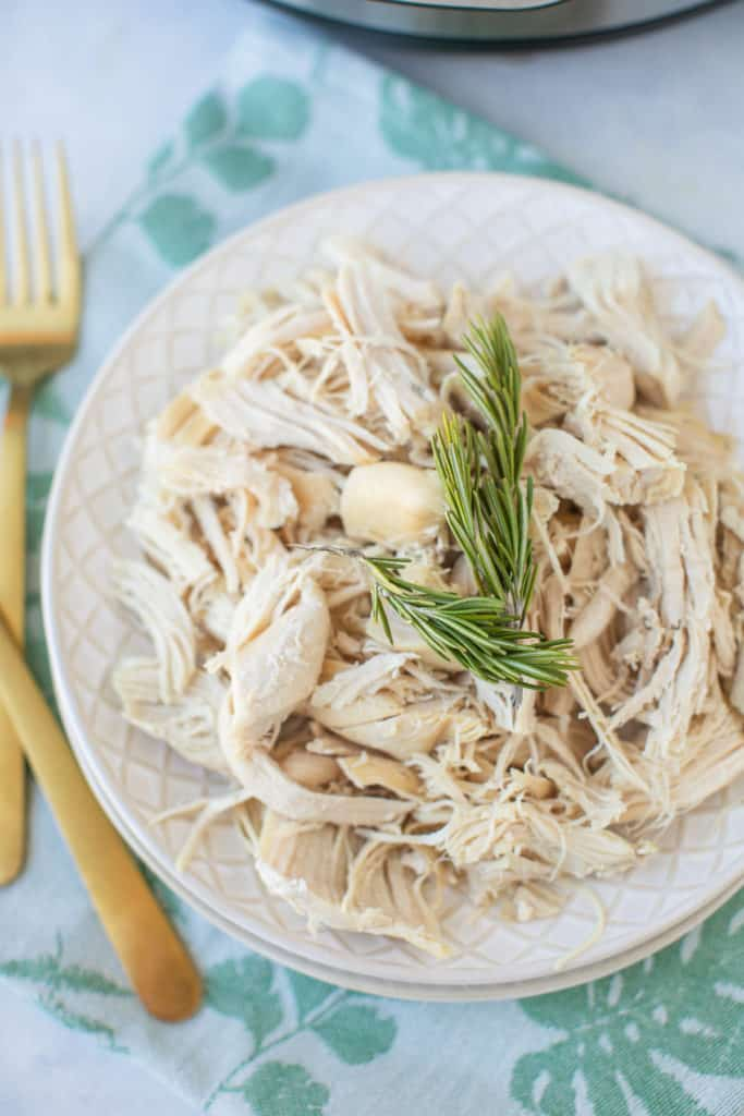 shredded chicken on a plate topped with fresh rosemary sprigs