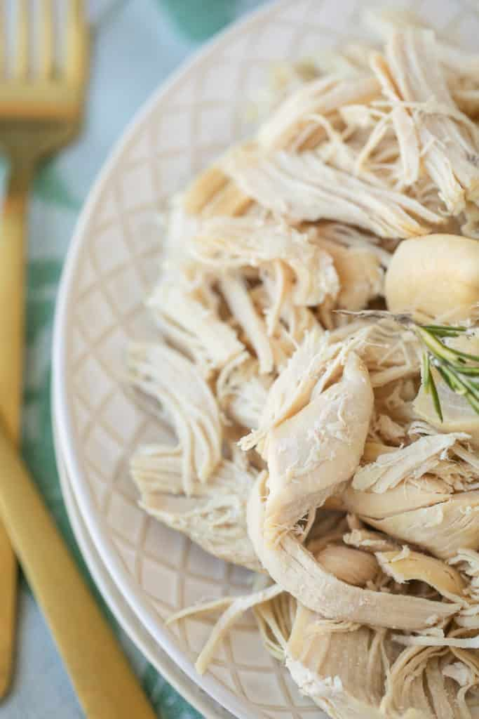 shredded chicken on a plate with a gold fork