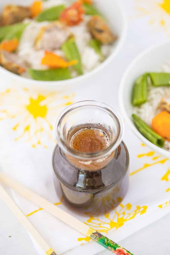 stir fry sauce with bowls of stir fried veggies and rice