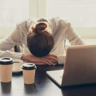 tired woman at laptop with coffee
