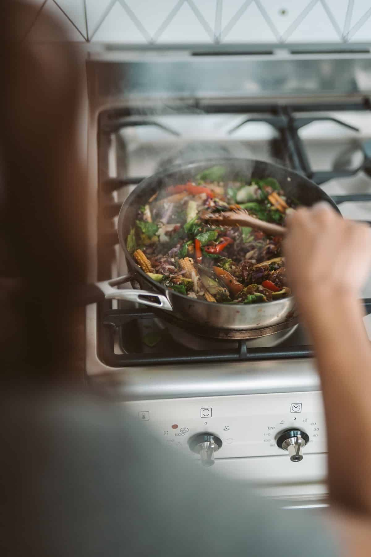 woman cooking stir fry in nonstick pan