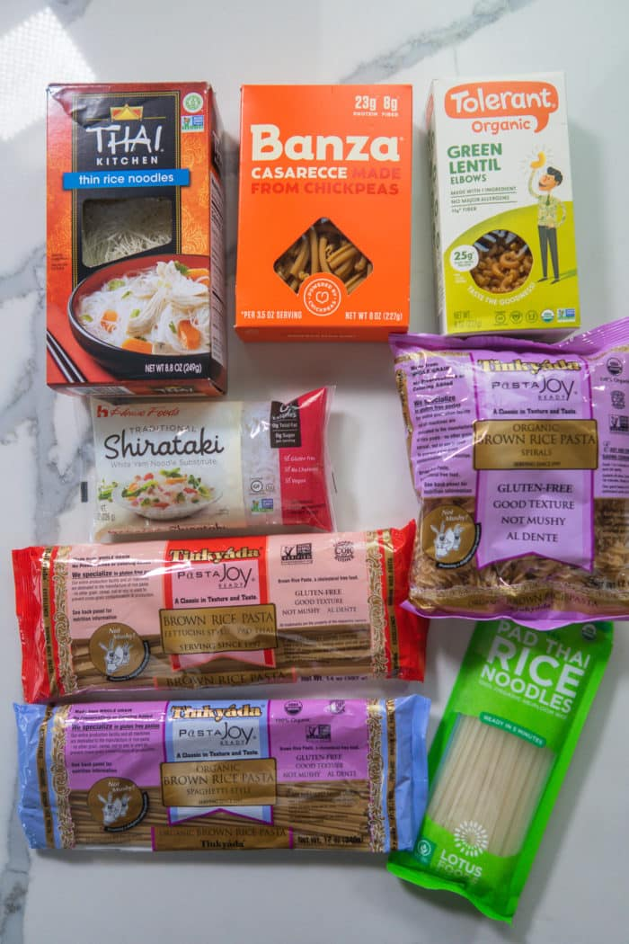 collection of many gluten free pasta brands on a kitchen countertop
