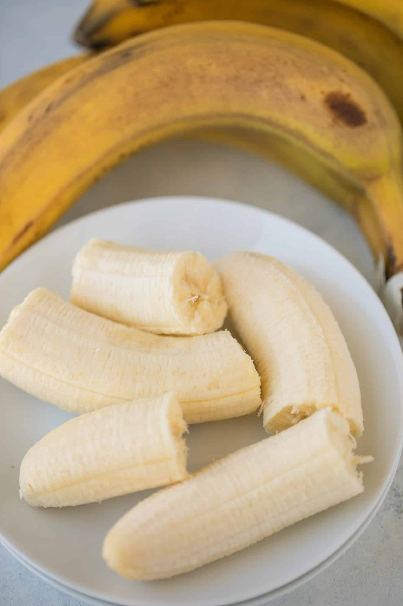 ripe bananas on a stack of white plates