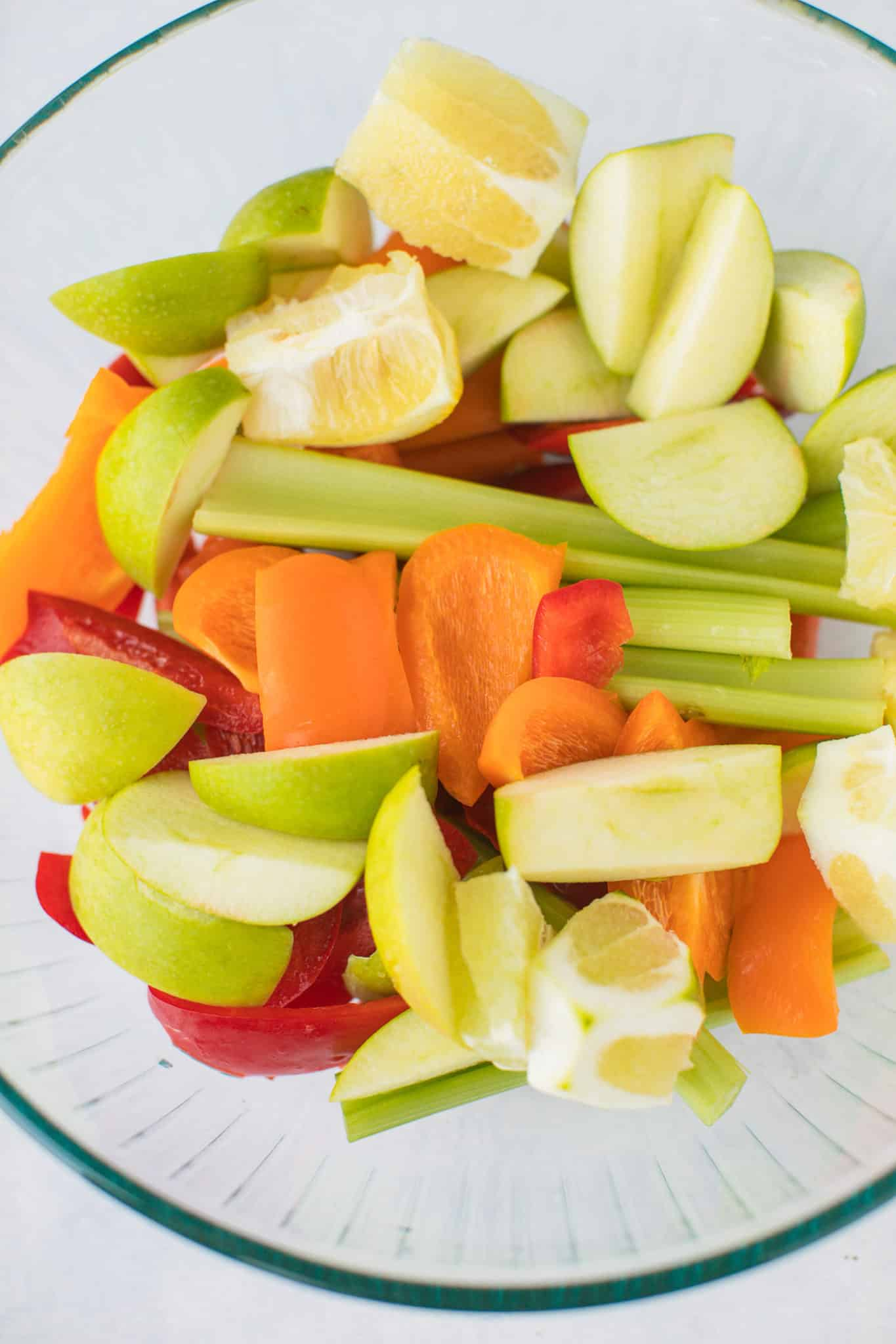 chopped apple, lemon, celery, carrots, and bell pepper for juicing