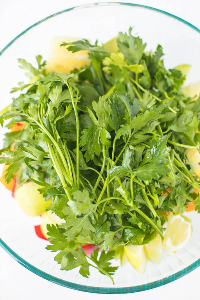 bowl of parsley and chopped veggies ready for juicing