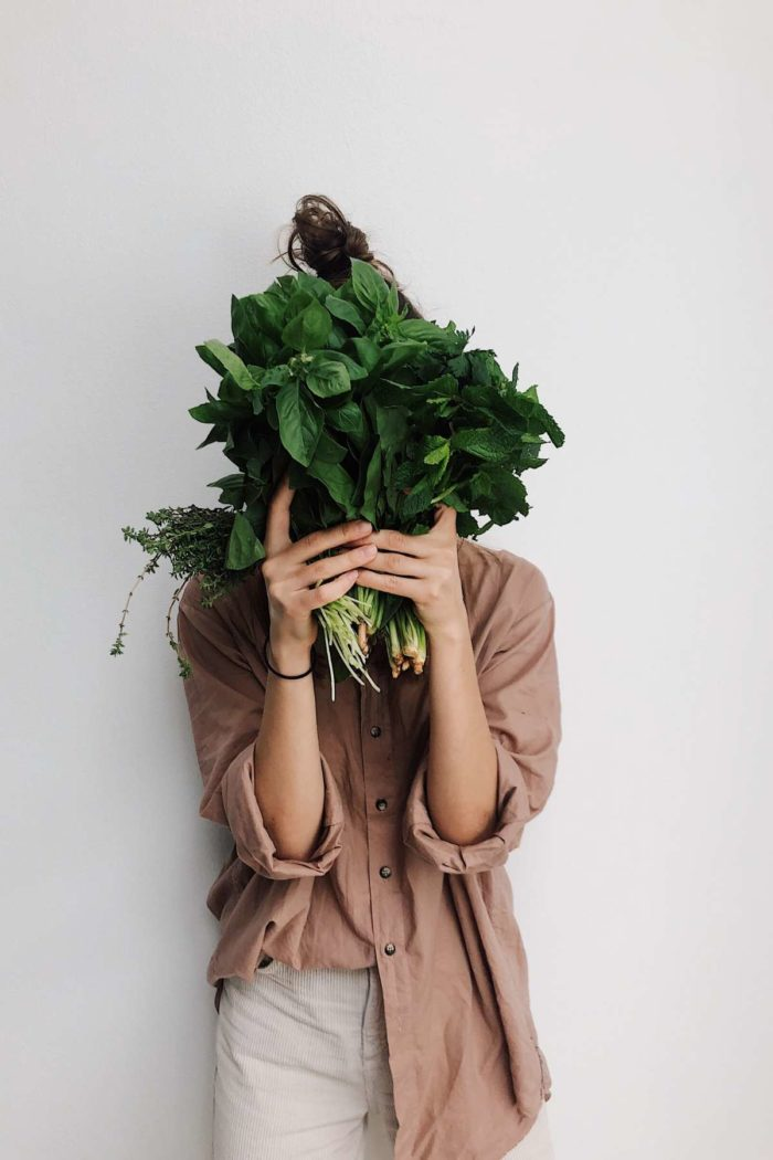 woman hiding behind greens