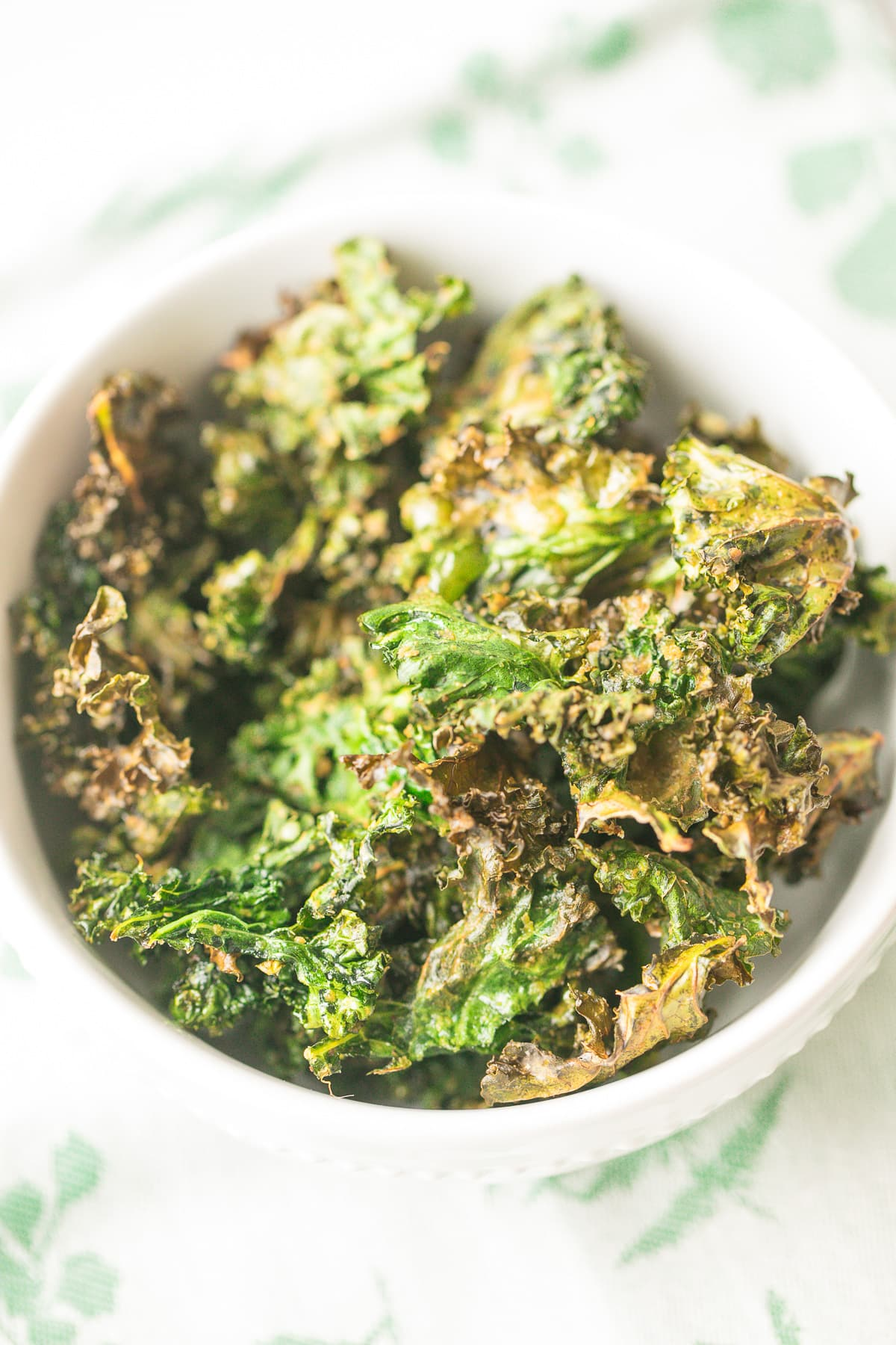 bowl of kale chips on top of a green and white napkin