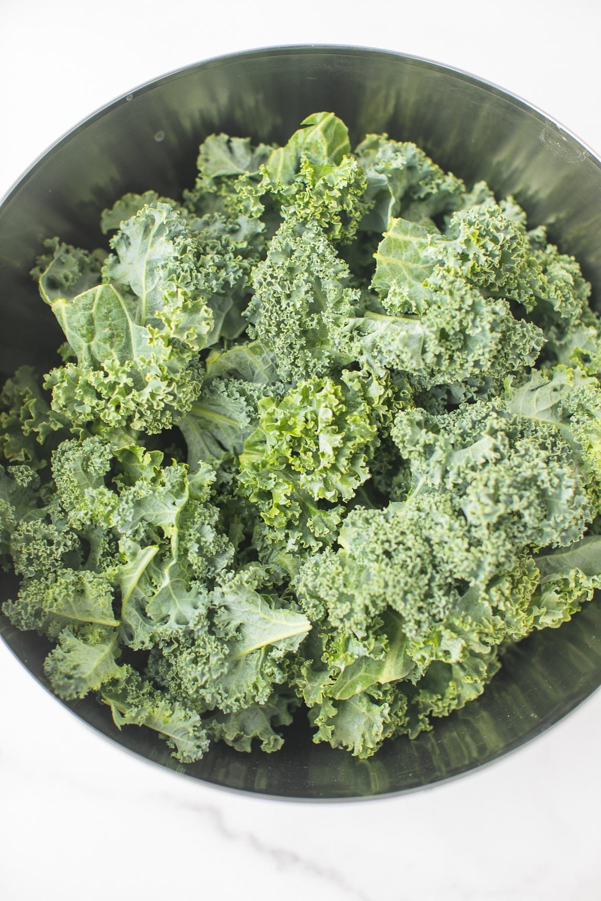 raw curly kale in a mixing bowl