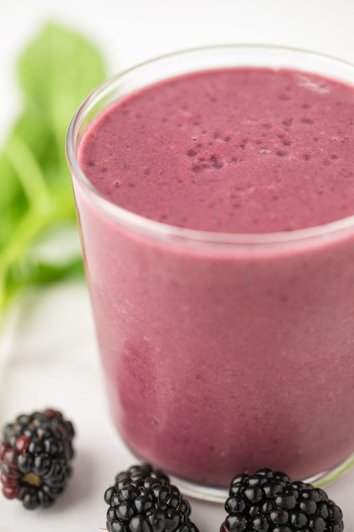 blackberry smoothie in a glass with three fresh blackberries