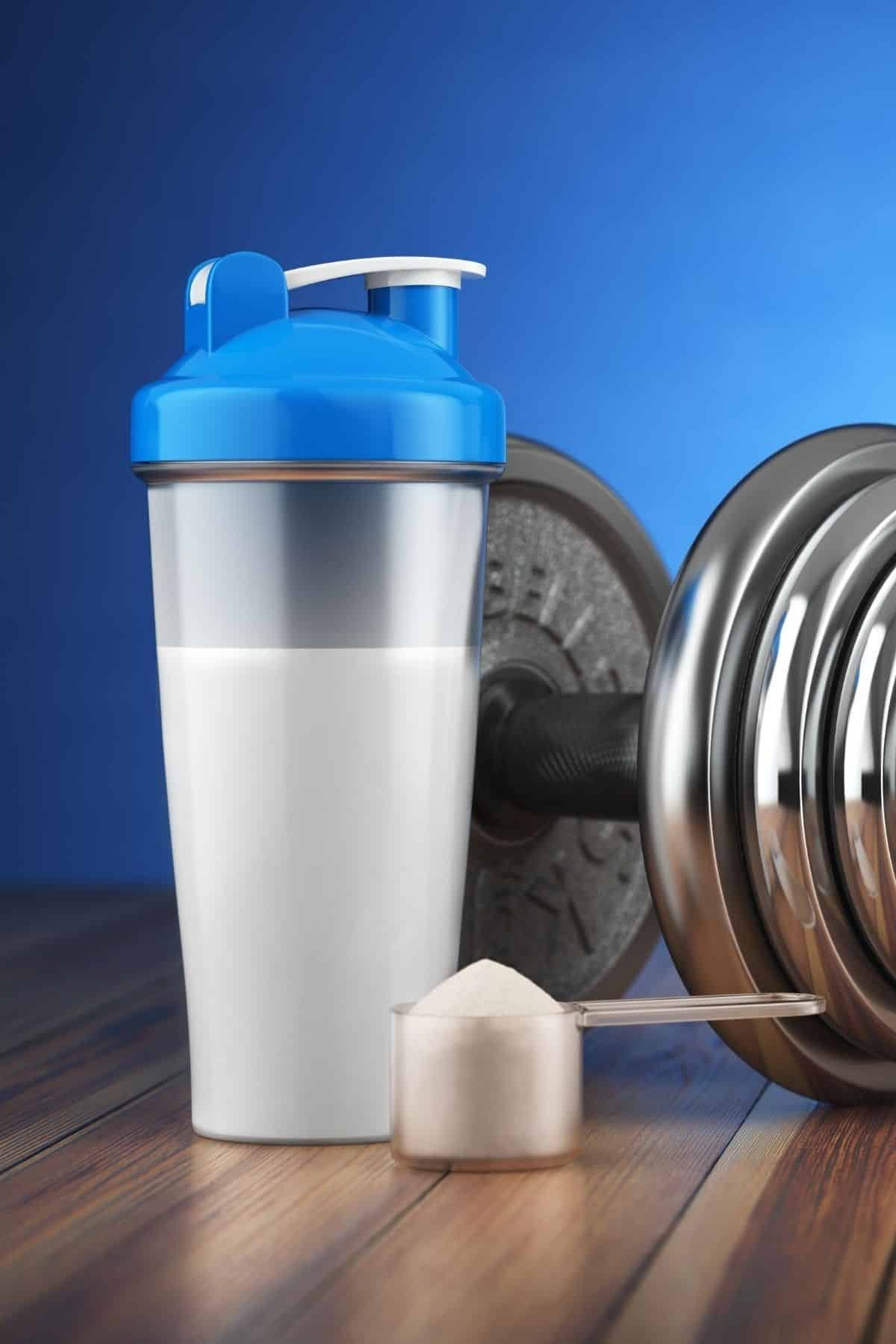 shaker bottle with a scoop of protein powder next to a dumbbell for working out