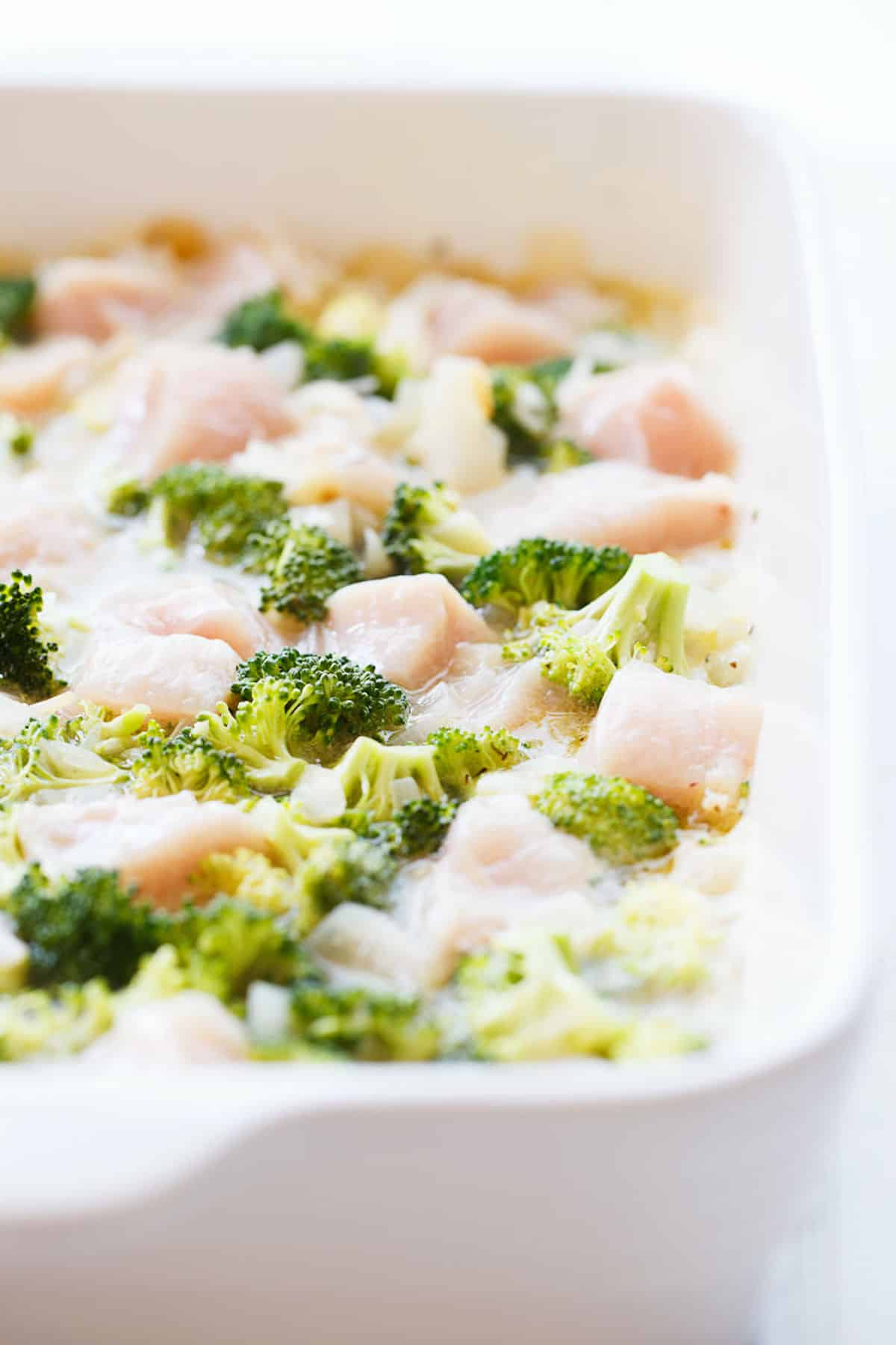 broccoli florets and chicken pieces in a casserole dish ready to be baked