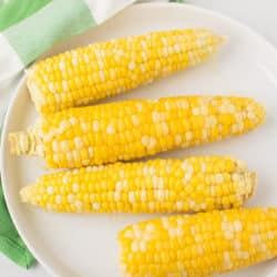 plate of corn on the cob on top of a green napkin