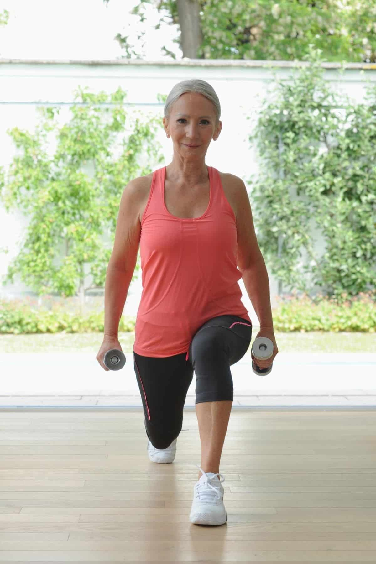older woman doing lunges with dumbbells in each hand