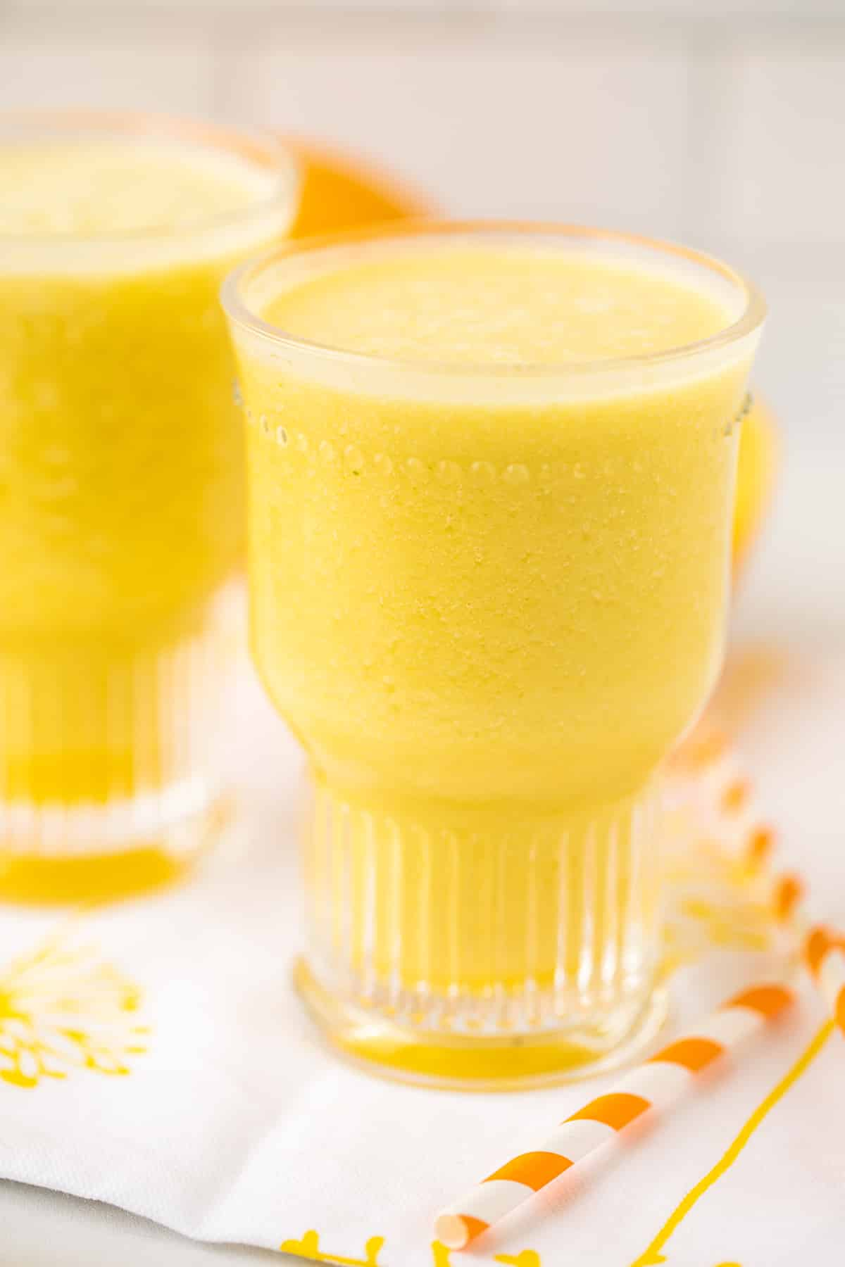 yellow smoothie with an orange striped straw