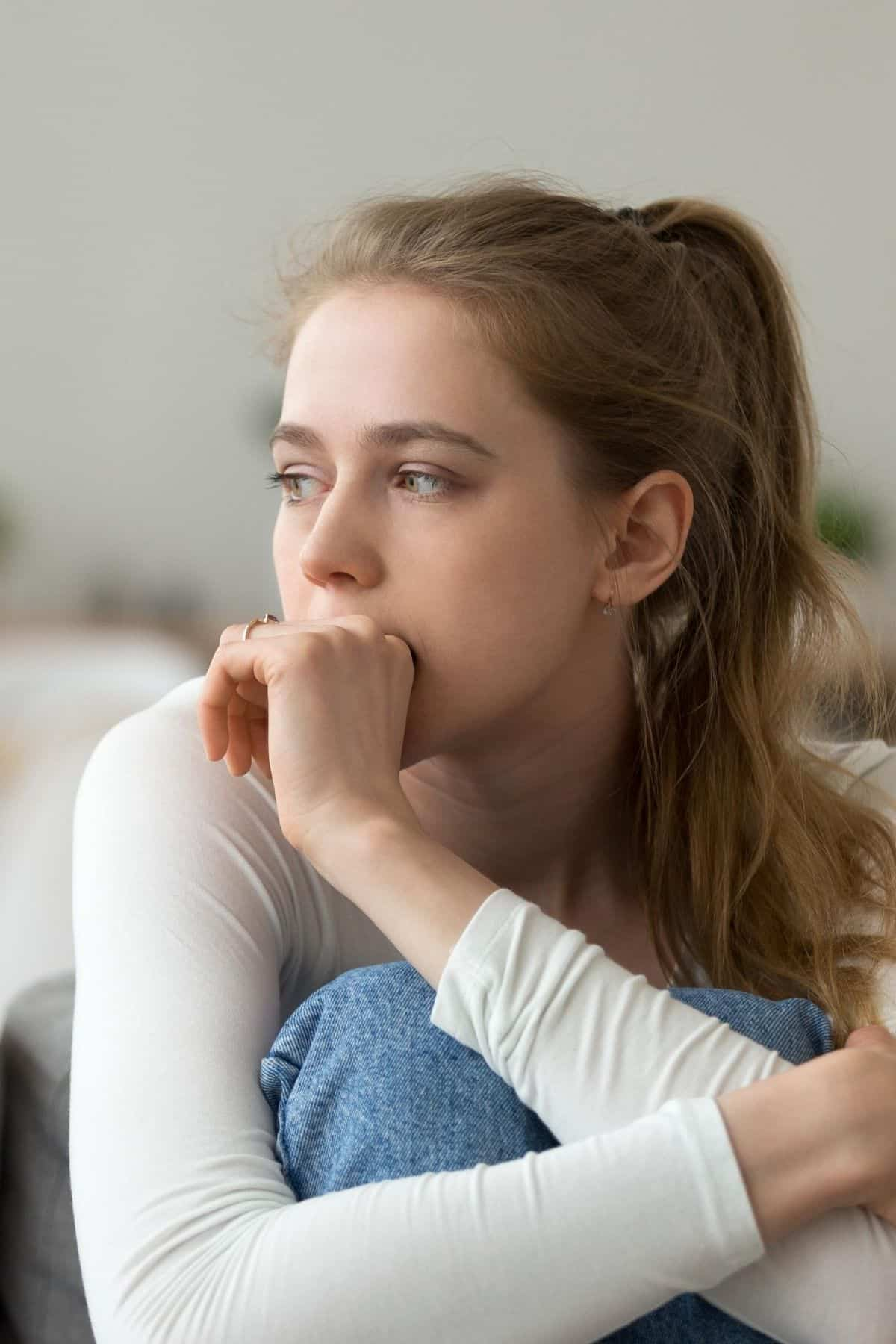 woman sitting on a chair with a worried look on her face