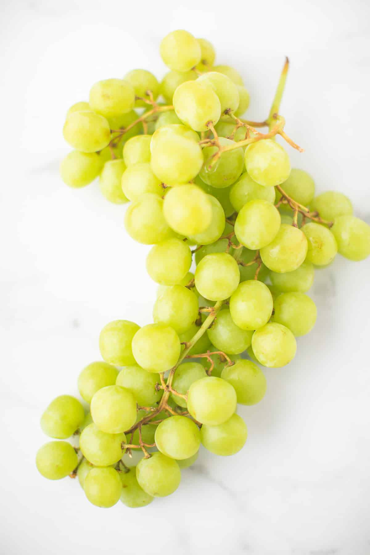 bunch of green grapes on a marble countertop