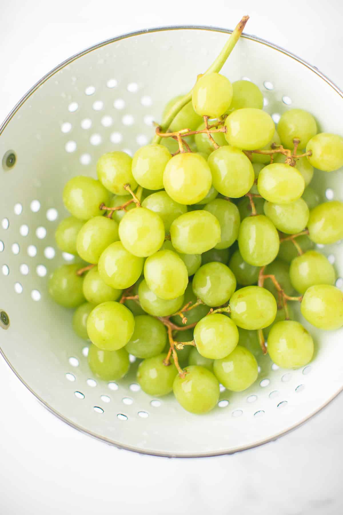 grapes being washed in a colander