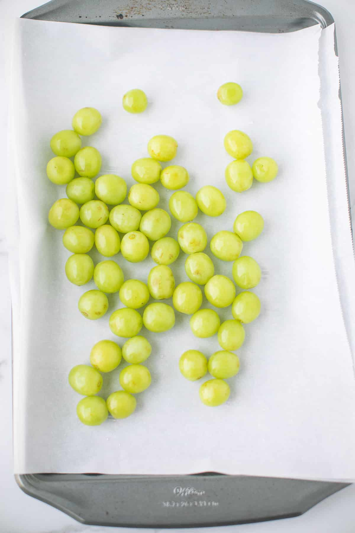 washed grapes on a baking sheet lined with parchment paper